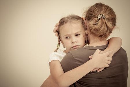 maltrato: hija triste abrazando a su madre Foto de archivo