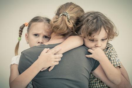 niños tristes: niños tristes que abraza a su madre Foto de archivo