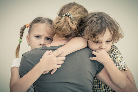 ni�os tristes: ni�os tristes que abraza a su madre Foto de archivo