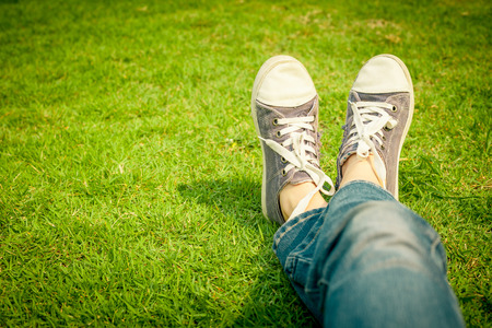 kids feet: youth sneakers on girl legs on grass during sunny serene summer day
