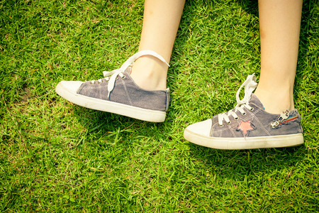 youth sneakers on girl legs on grass during sunny serene summer day  photo