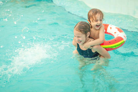 two little kids playing in the pool photo