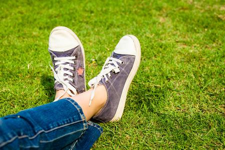 青少年に晴れた穏やかな夏の日の間に草の上の女の子の足上のスニーカー