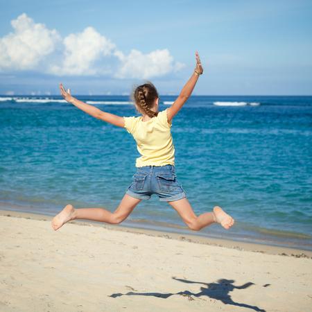 niño corriendo: volar niña saltando en la playa azul orilla del mar en las vacaciones de verano durante el día Foto de archivo