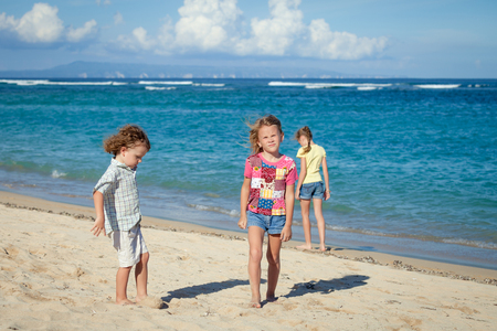 strolling: happy kids playing on beach in the day time Stock Photo
