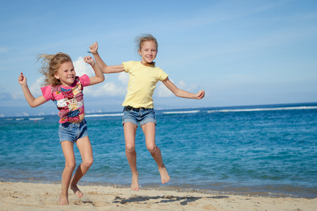 happy little girls jumping on beach in the day time photo