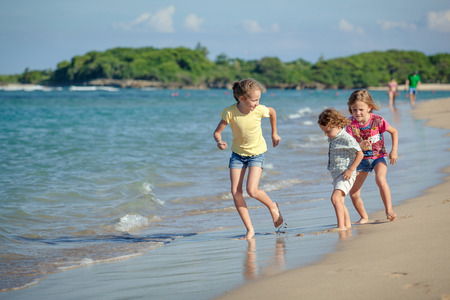 happy kids playing on beach in the day time photo