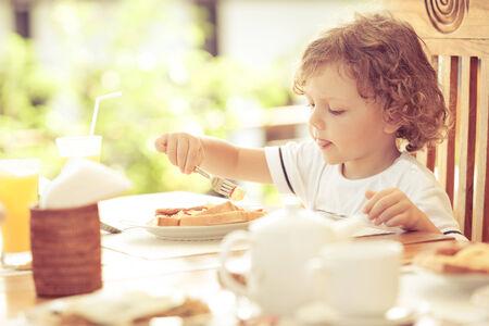 niños desayunando: niño en el desayuno