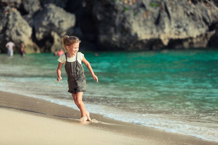 Happy little girl walking at the beach in the day time photo