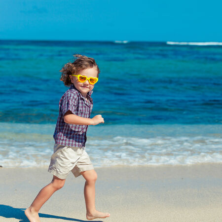little boy running on the beach in the day time photo
