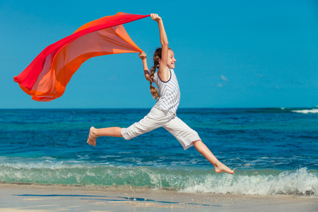 teen girl  jumping on the beach at blue sea shore in summer vacation in the day time photo