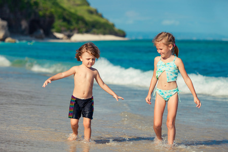 two little kids playing at the beach in the day time photo
