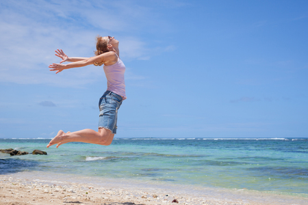 woman jumping at the beach in the day time photo
