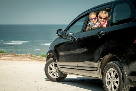 two sisters sitting in a car on the beach photo