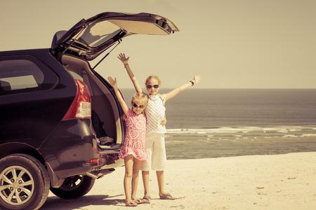 tourist vacation: due sorelle piedi vicino a un auto sulla spiaggia Archivio Fotografico