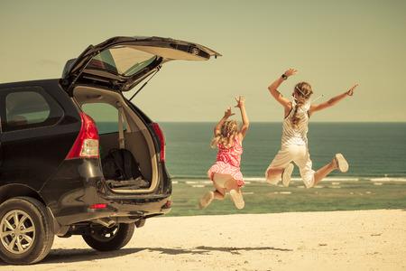 twee zussen staan in de buurt van een auto op het strand Stockfoto