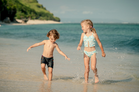 two little kids playing at the beach at the day time photo