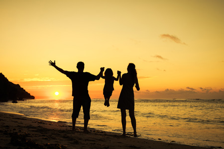 Happy family playing at the beach in the dawn time photo