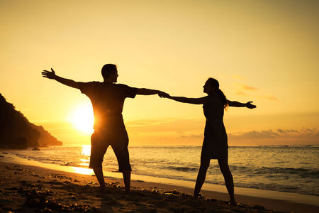 Happy family standing on the beach at the dawn time photo
