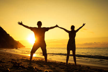 couple having fun: Happy family standing on the beach at the dawn time