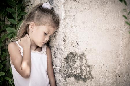 niños tristes: Retrato de niña triste que se coloca cerca de la pared de piedra en el tiempo del día