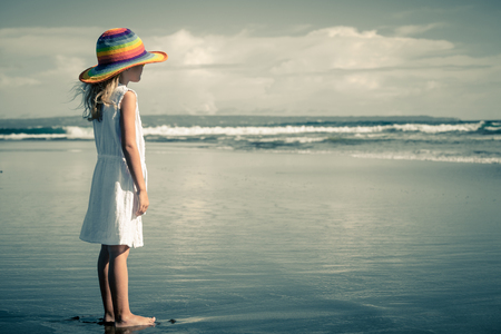 Sad little girl standing at the beach in the day time photo