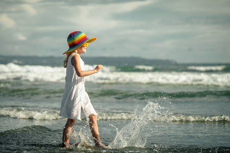 Happy little girl in the hat walking at the beach in the day time photo