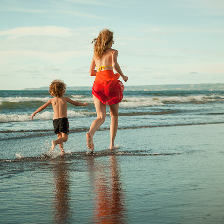 mother and  son playing on the beach in the day time photo