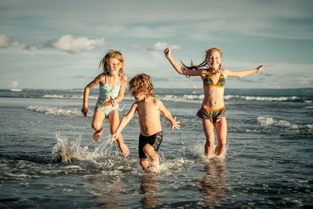 kids playing water: happy kids playing on beach in the day time Stock Photo