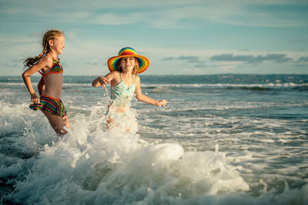 two sisters splashing on the beach in the day time photo