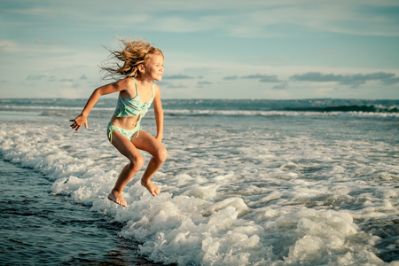 little girl jumping on the beach in the day time photo