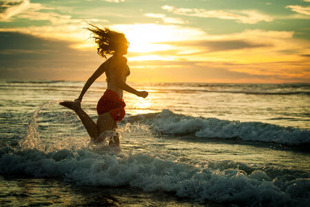woman running at the beach in the dawn time photo