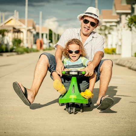 father and little son playing near a house at the day time photo