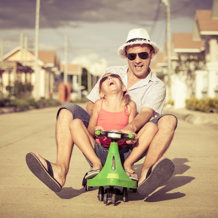 father and little daughter playing near a house at the day time Stock Photo