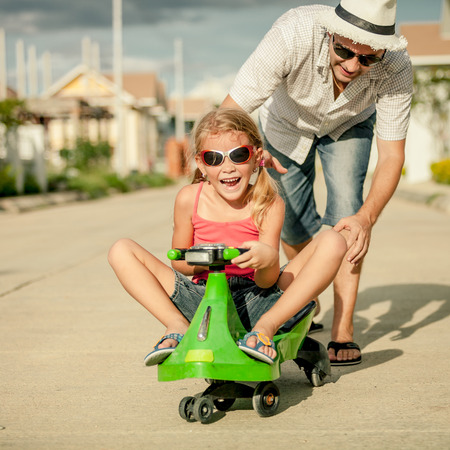 father and little daughter playing near a house at the day time photo