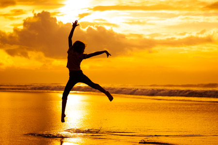 Happy girl jumping on the beach on the dawn time photo