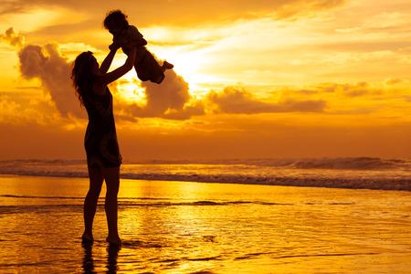 silueta ni�o: madre e hijo jugando en la playa en el tiempo del amanecer