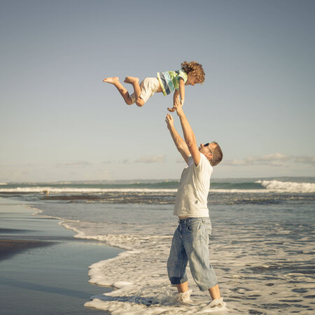 father and son playing on the beach in the day time photo
