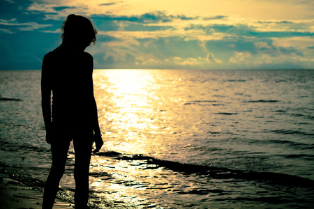 sad teen girl standing on the beach at the dawn time Stock Photo