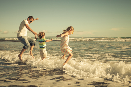 father, daughter and son playing on the beach at the day time photo