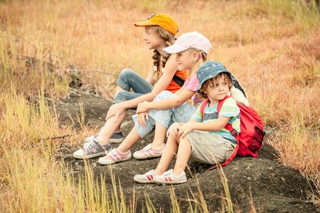 Trzy małe dzieci z plecak siedzi na chodniku w górach