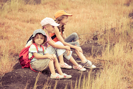 three little kids with backpack sitting on the footpath in the mountains photo