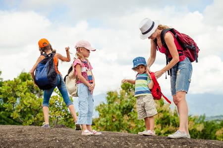Drie kleine kinderen en moeder in de bergen