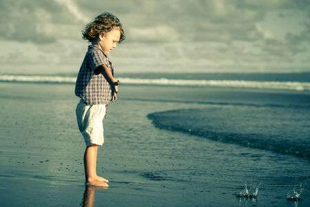 little boy playing on the beach at the day time photo