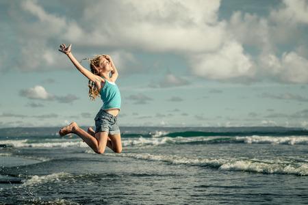 tiener meisje springen op het strand op blauwe zee kust in de zomer vakantie op de dag de tijd