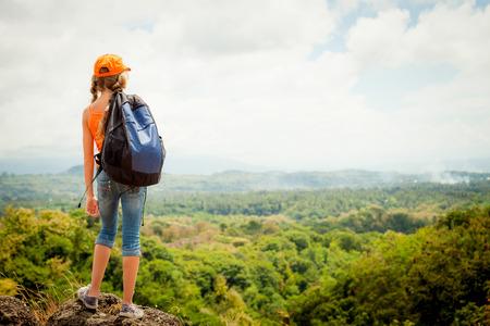 niño con mochila: adolescente con una mochila de pie en la cima de la montaña