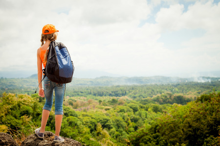 teenager with a backpack standing on a mountain top Stockfoto