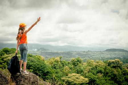 tiener met een rugzak staande op een berg top Stockfoto