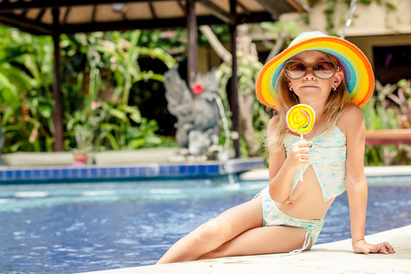 little girl with lollipop sitting near the swimming pool Banco de Imagens