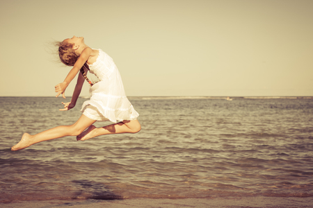 teen girl jumping on the beach at the day time photo